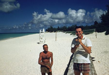 jack-lemmon-filming-slim-aarons-taking-picture-of-him-on-beach-in-hawaii-during-filming-of-mister-roberts-henry-fonda-looks-on1955
